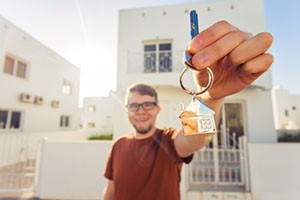 man with key to house after obtaining a first time home buyer loan