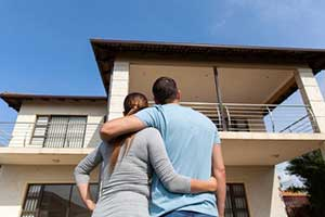 Couple in front of new home after signing a Woodbridge, VA first time home buyer loan