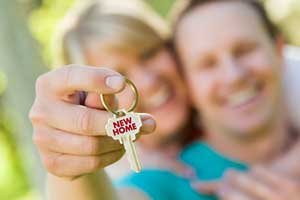 Couple showing key to new home after signing a Sterling, VA first time home buyer loan