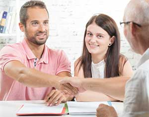 Couple signing paperwork for their first time home buyer loan