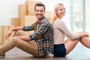Couple sitting in new home after acquiring a Fairfax, VA first time home buyers loan