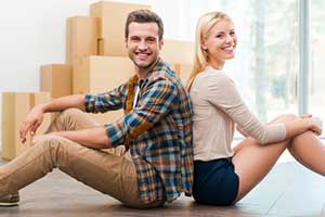 Couple sitting in new home after acquiring a Fairfax, VA first time home buyer loan