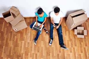 Couple sitting on floor in new home after Vienna, VA first time home buyer loan assistance