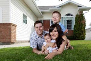 Family in front of new home after receiving a VA military home loan