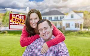Happy couple in front of new home after signing a Stafford, VA first time home buyer loan