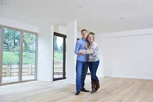 Happy couple standing in new home after signing a Dale City, VA first time home buyers loan