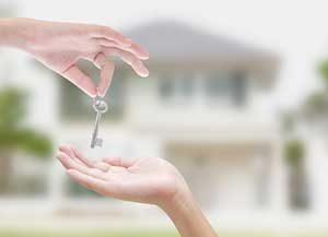Woman being handed keys after assistance from an Ashburn, VA first time home buyers loan
