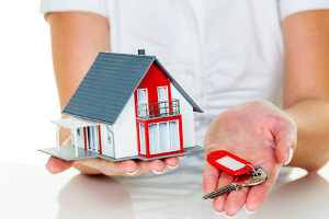 mortgage broker holding a model house and keys to signify a jumbo loan