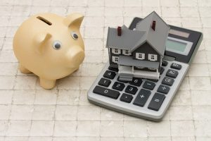 model home, calculator, and piggy bank representing an FHA loan down payment