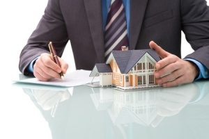 mortgage broker signing paperwork to issue a mortgage for a person with bad credit