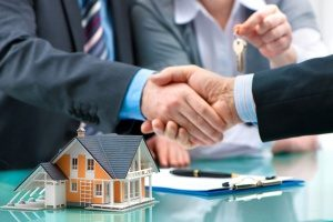 local mortgage broker shaking hands with a person buying a new home with an FHA Section 203(k) loan