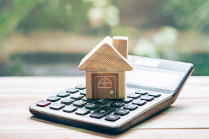 Wooden home on top of calculator representing calculating tax deductions for mortgage insurance