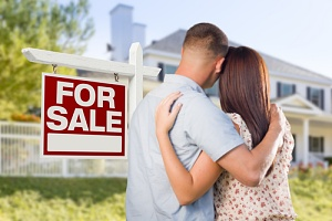 couple standing outside a house for sale