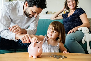 family putting extra money into piggy bank after getting a second mortgage