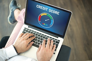 person sitting with laptop checking their credit score
