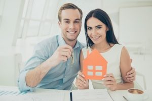 a couple holding a model home after signing up for a bridge mortgage loan