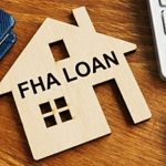 a wooden block home with the words FHA loan on it on a table