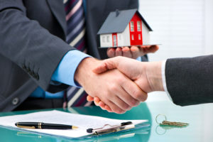 mortgage broker shakes one of the first time home buyers hand after approving their mortgage loan
