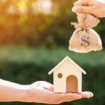 A money bag and a model home. Be prepared and informed before taking out a home loan