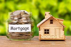 A jarful of coins and a model of home. Be sure to ask questions before taking out a Home Loan