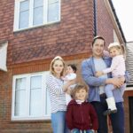 first time home buyer and family stand in the front of their newly bought home