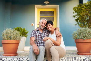 first time home buyer and spouse smile and sits on the porch of their new home