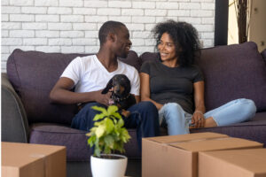 first time home buyer, spouse and dog sit in their new home