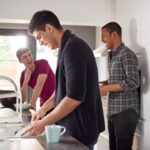 college students in shared house kitchen washing